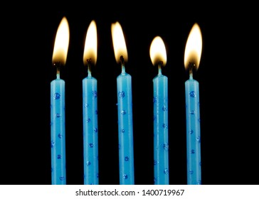 Five blue burning birthday candles on black background