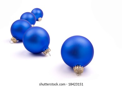 Five blue Christmas Tree ornaments on a field of white.