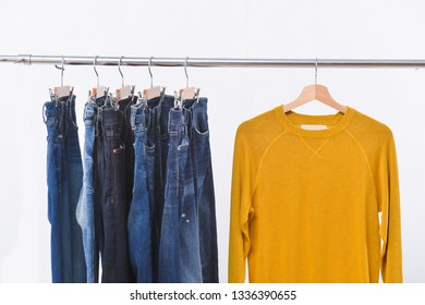 Five blue jeans and yellow.sweater clothes on hanger-