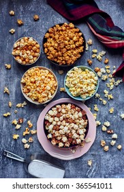 Five bowls of various flavored popcorn. Popcorn from above.