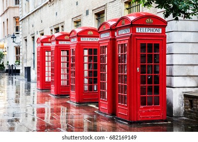 Five British red phone boxes in a row. A line of phone booths in Covent garden, London, after the rain.