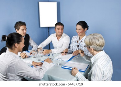 Five business people around a table at meeting laughing together and looking to paperwork of a businesswoman,blank chart or white board in background were you can type your text