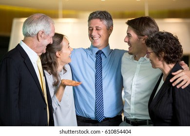 Five Business People Embracing and Laughing