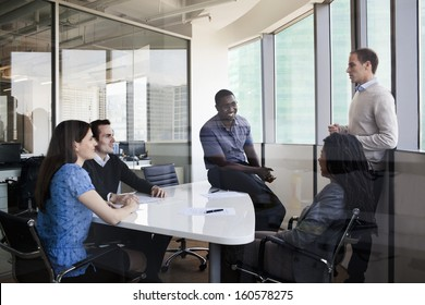 Five business people sitting at conference table and discussing during business meeting