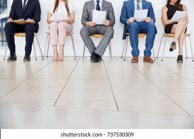 Five candidates waiting for job interviews, front view, crop