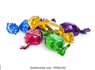 Five candies wrapped in colored foil on white background