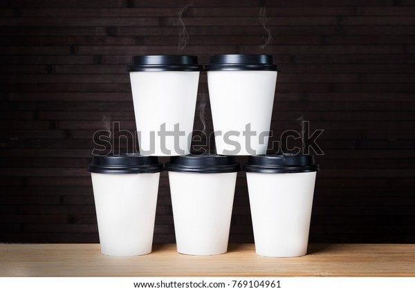 Five cardboard coffee glasses on each other with smoke on a black background