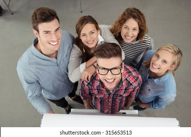 Five Cheerful Young Workmates Smiling at the Camera from High Angle View Inside the Office.