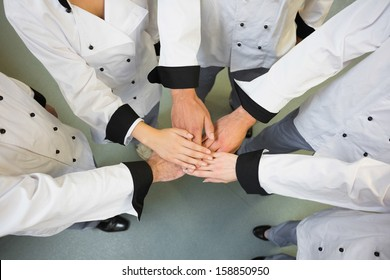 Five chefs joining hands in a circle wearing uniforms