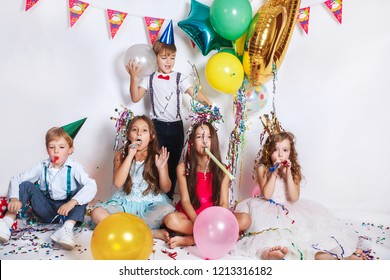 Five children. Positive relaxed pretty kids sitting together at the birthday party and blowing lovely party horns