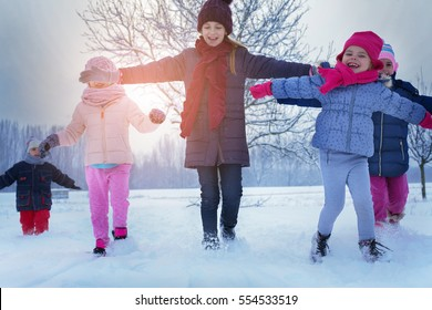 Five children run and play in a snow.