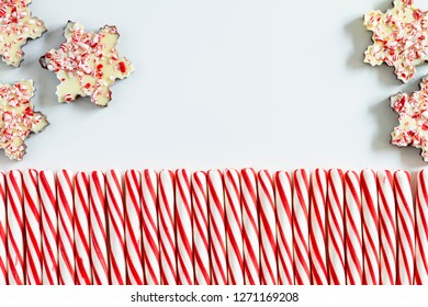 Five chocolate peppermint bark snowflakes with row of red and white striped peppermint candies
