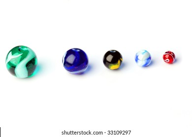 Five colored glass balls known as marbles, on white