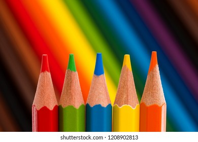 Five colored pencils on colorful background