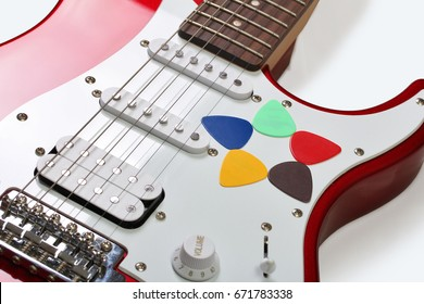 Five colored picks on a guitar on a white background