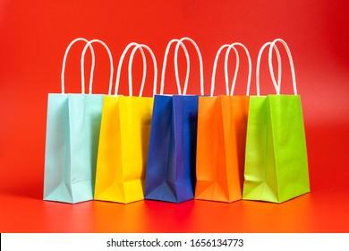 Five colorful gift or shopping bags isolated on red background
