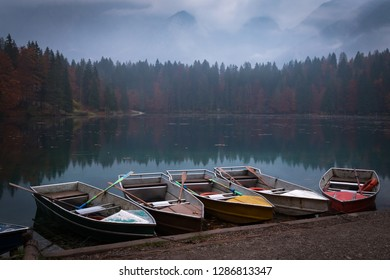 Five colorful small boats on a rainy evening in lake Laghi di Fusine near Tarvisio in Italy, Europe