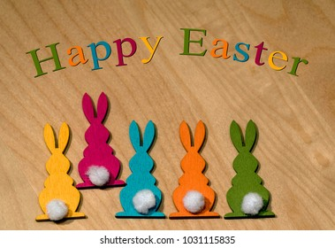 Five colorful wooden Easter bunnies in a row and one of them is dancing out of line - Easter greetings in English