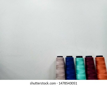 Five colourful thread cones on the corner of the white background. Thread colour nude, blue navy, mint, red and orange