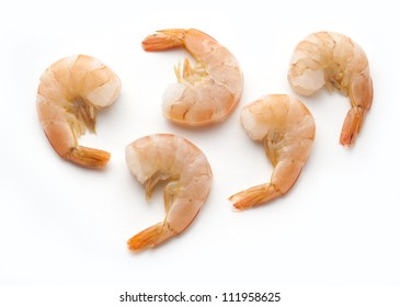 Five cooked shrimp with tails isolated on white background.