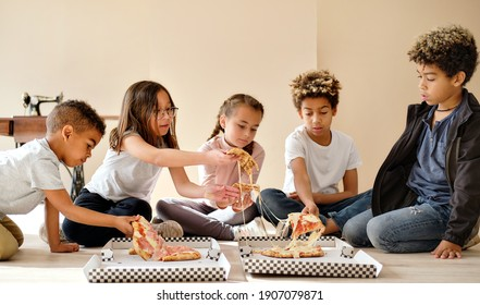 Five cute multiracial children little boys and girls sit indoor eating pizza italian fast food cuisine. Alpha generation share slices, spend time together. Friendship, time-to-eat lunch time concept
