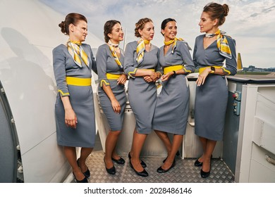 Five cute stewardesses conversing on the boarding stairs