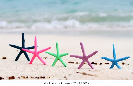 Five different colored Star fish placed upright on a beautiful tropical beach, with the aqua ocean with waves in the background.