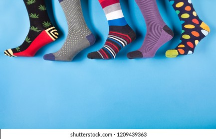 five different men's socks in a row on a pastel blue background
