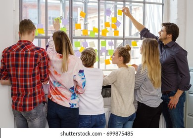 Five different people standing in front of a large window covered by many small multicolored sticky notes