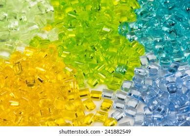 five different translucent polymer pellets for injection moulding