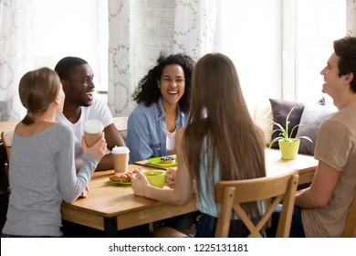 Five diverse students sitting around the table drinking coffee having fun communicating laughing together. Millennial multiracial different friends guys and girls talking enjoying conversation in cafe