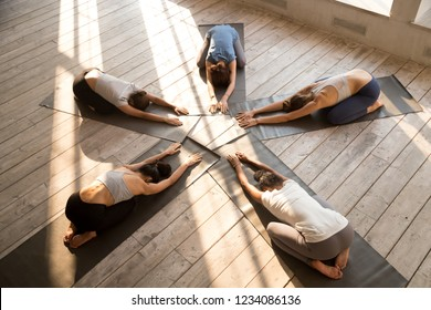 Five diverse young women lying in circle on rubber black carpets in modern sports studio in the morning performing Child Pose, relaxing breathing during yoga session. Group training, wellness concept