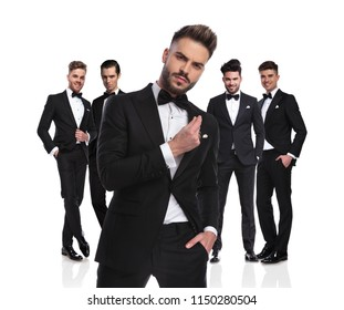five elegant groomsmen standing on white background, dressed in black tuxedoes,with arrogant leader in front