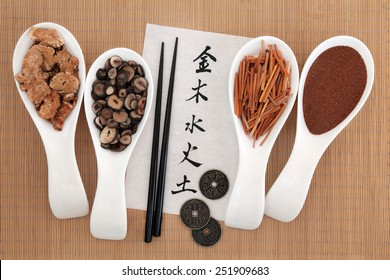 Five elements chinese calligraphy script on rice paper with herbal medicine selection. Metal, wood, water, fire, earth characters, top to bottom.