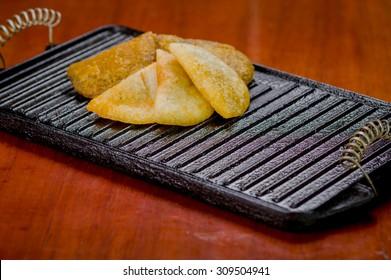 Five empanadas lying in fan formation on black metal grill tablet.