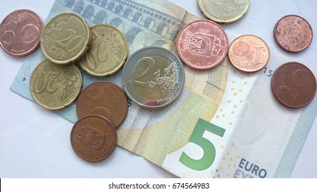 Five euro bank note and euro coins