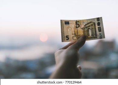 Five euro in hand over city background.