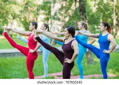 five European women in colored outfits for yoga exercise on the lawn in the Park on rugs