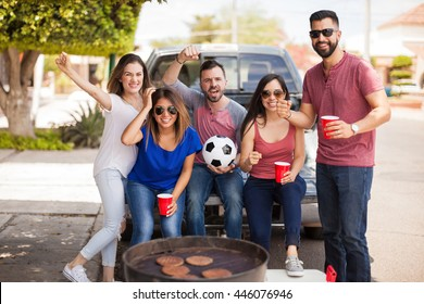 Five excited soccer fans and friends watching a game while grilling some burgers and drinking beer
