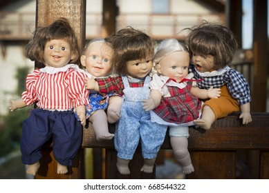 Five expressive dolls stand in a wooden box