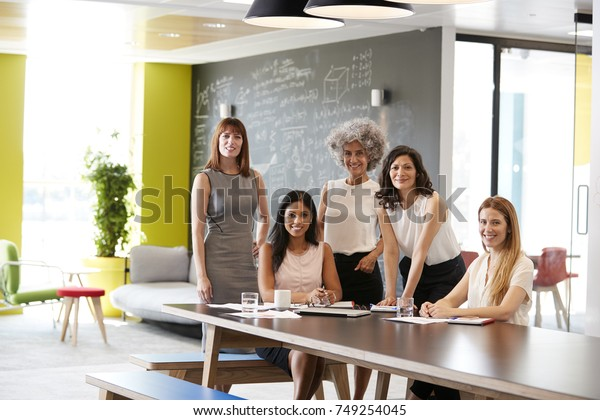 Five female colleagues at a work meeting smiling to camera