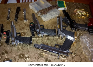 five firearms on the table with tool box, two barrels and bullets