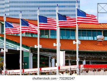 Five flags waving patriotically with red, white, and blue stars and stripes.