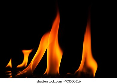 Five flames, two small and three large with a reflection in the ground, isolated against a black background. Horizontal view.