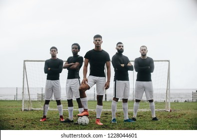Five football players standing in a formation in front of goalpost. Soccer player standing with one foot on ball with teammates standing behind him with arms crossed.