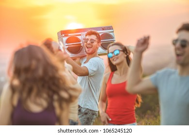 The five friends with a boom box dancing on the sunrise background