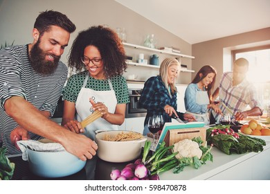 Five friends cheerfully cooking for an upcoming party