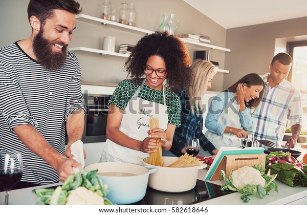 Five friends cooking at kitchen, having a lot of fun