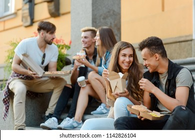 Five friends are dining together outdoors. Wok noodles, hamburger, frites and pizza. Eating street food concept.