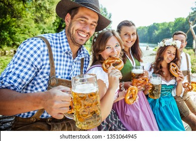 Five friends having fun on Bavarian RIver with beer glasses.